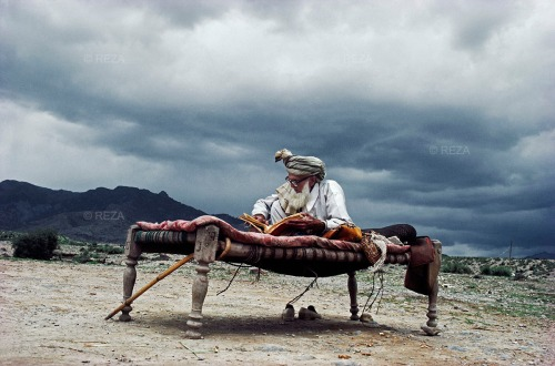 1983  Afghanistan. During the Soviet invasion of Afghanistan (1979-1989), an old Afghan man in exile reads the Koran, seated on a bed in the middle of the mountains at the Afghan-Pakistani border.  Afghanistan. Pendant la guerre d'Afghanistan (1979-1989), un vieil homme afghan en exil lit le Coran, assis sur un lit au milieu des montagnes ‡ la frontiËre pakistano-afghane.