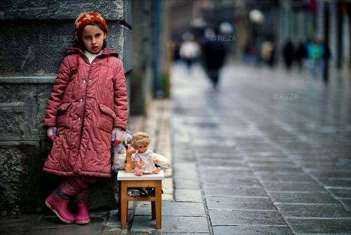 Bosnie. Sarajevo. DÈcembre 1993 L'air Ètait glacÈ, la ville respirait au rythme des sursis accordÈs. Les rues dÈsertes s'animaient parfois de la course folle de celui qui risquait sa vie pour un peu d'eau, pour une miche de pain, sous le regard des snipers. Elle Ètait l‡, immobile petite touche de couleur dans la grisaille froide de la guerre. Sans un mot, sans un geste, elle vendait ses jouets, tÈmoins d'une vie perdue. Je me suis senti profondÈment dÈmuni, face ‡ cette injustice de l'HumanitÈ qui contraignait une fillette ‡ vendre ce qu'elle avait de plus prÈcieux, ses compagnons, ses garants de l'enfance. C'Ètait dans Sarajevo assiÈgÈe que je l'ai vue lutter en silence. Bosnia. Sarajevo. December 1993 The air was chilling, and the city breathed to the rhythm of granted sentence respites. The deserted streets would sometimes come to life as a man ran wild risking his life for a little water or a loaf of bread under the snipers' eyes. She was standing there, like a motionless color stain in the cold dreariness of war. Without a word, without a move, she was selling her toys, testimony of a wasted life.  I felt quite helpless facing such human injustice that forced a little girl to sell what was dearest to her, they were her companions, her childhood's guarantors. I saw her fighting silently in besieged Sarajevo.